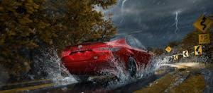 Red Toyota Camry Hybrid driving through the rain